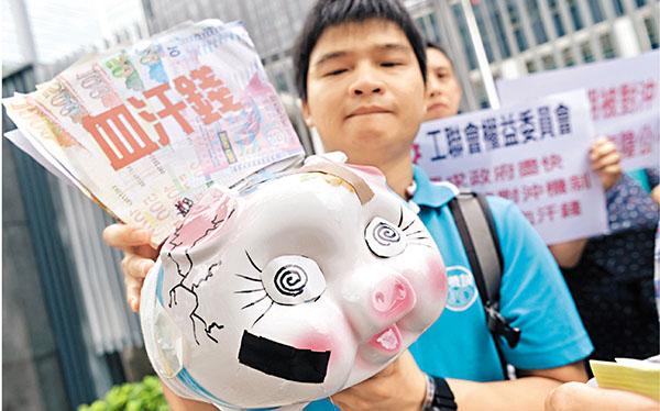 ■市民手持有裂痕的豬仔錢罌遊行,寓意要守住強積金儲下的「血汗錢」。