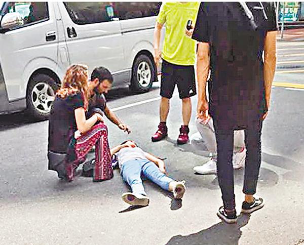 ■遭的士撞傷女子倒臥地上,兩名外籍男女上前安慰。 網上圖片