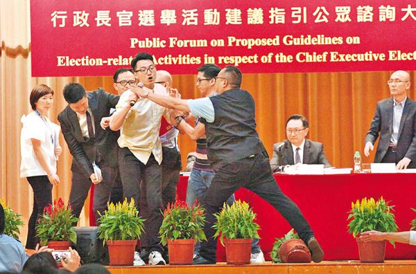 ■鄭錦滿衝上講台,被保安員制止。 曾慶威  攝