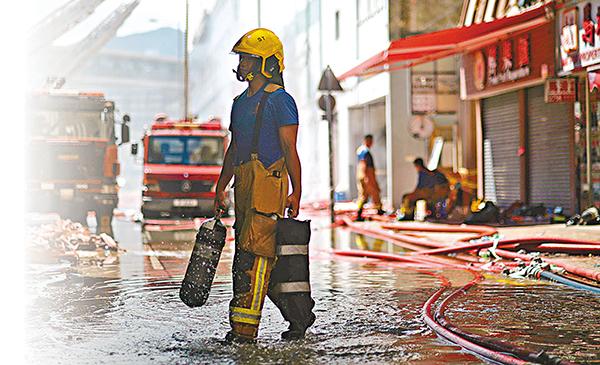 ■火場現已受控,消防員終於可以休息了。梁祖彝  攝