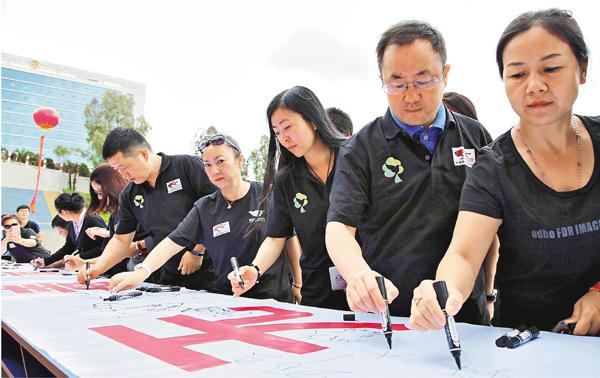 ■禁毒義工在禁毒宣傳布標上簽名。記者丁樹勇  攝