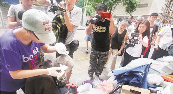 ■市民李小姐(左一)為「睡婆婆」清洗傷口及重新包上紗布。