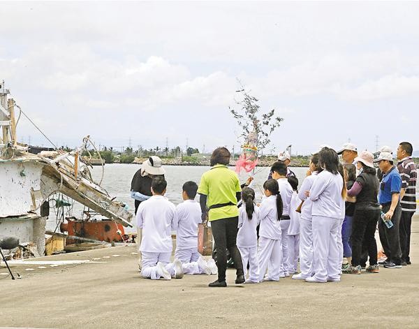 ■因飛彈誤射枉死的漁船船長家屬到停泊「翔利昇號」漁船的碼頭,進行招魂法事。 中央社
