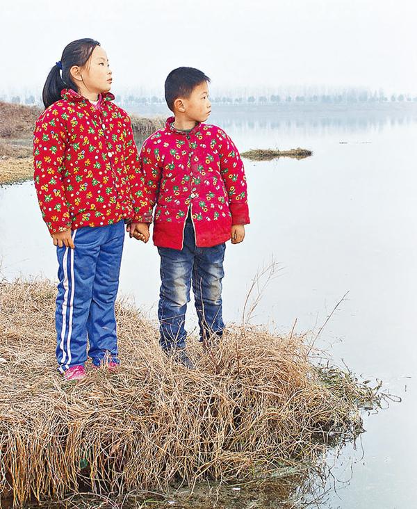 ■在安徽省阜陽市八里河鎮,9歲的馬舒文和弟弟(左圖)站在家鄉的湖邊,馬舒文的父母則在浙江杭州西湖邊(右圖)。一年裡,他們一家只在春節和暑假團聚兩次。 資料圖片