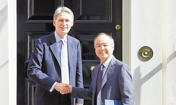 ■軟銀社長孫正義(右)與英國新任財相夏文達握手。法新社