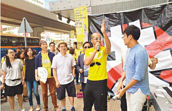 ■黃洋達昨日竟聲稱「香港建國」等口號「符合基本法」。陳雲(戴帽者)公然恐嚇選舉主任要「小心做人」。