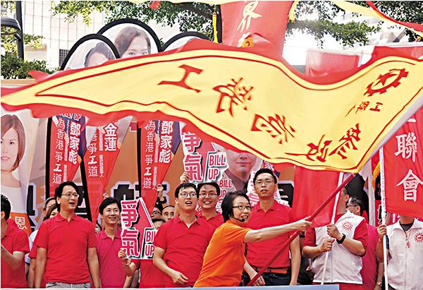 ■嫻姐揮旗為工聯會助威。 莫雪芝  攝