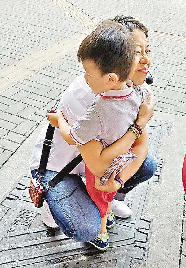 ■有小朋友與麥美娟緊緊相擁,溫情滿滿。