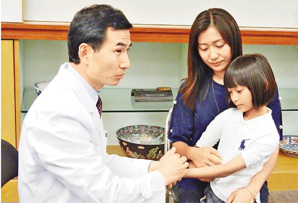 ■孫素明(左一)在子悠手腕示範小兒推拿療法。子悠身後為其母趙太。 黎忞 攝