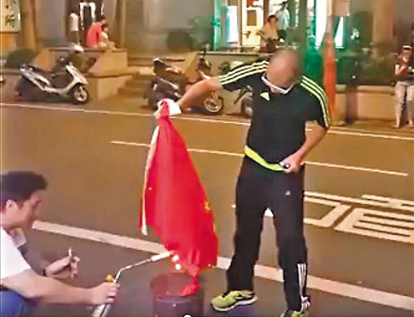 ■黃洋達等人將一面中國國旗放進了化寶桶裡焚燒。 視頻截圖