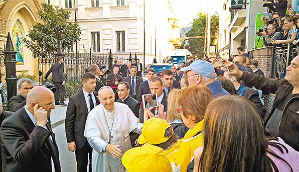 ■教宗在市中心的聖母升天大教堂外與各人握手。 黎耀康 攝