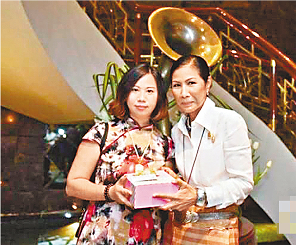 ■泰國旅遊和體育部部長葛甘(右)向為中國遊客捐「熊貓血」的南京女導遊楊莉贈送紀念品。網上圖片