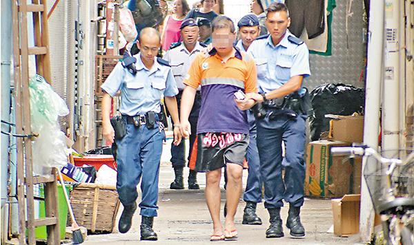 ■警員在兇案現場後巷帶走一名涉案男子。