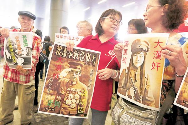 ■示威民眾手舉游蕙禎、梁頌恆「身穿」日寇軍服海報,譴責二人辱國辱族。
