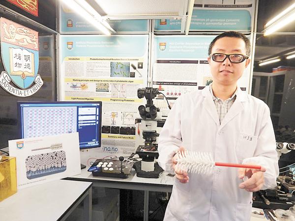 ■圖為唐晉堯手持放大三萬倍的機械人模型,以及利用顯微鏡放大展示機械人。 黎忞  攝