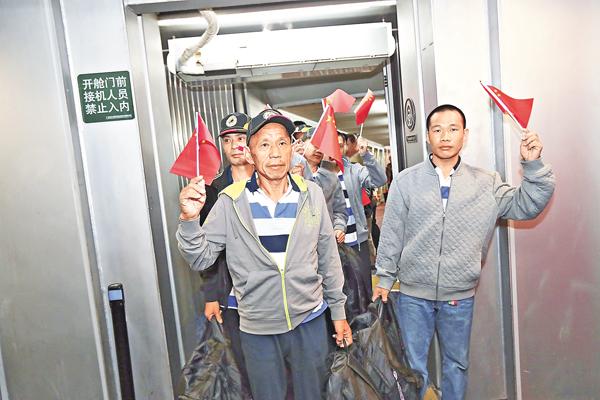■遭索馬里海盜綁架的中國船員獲救,乘專機抵達廣州白雲機場,並手持國旗走出艙門。 本報廣州傳真