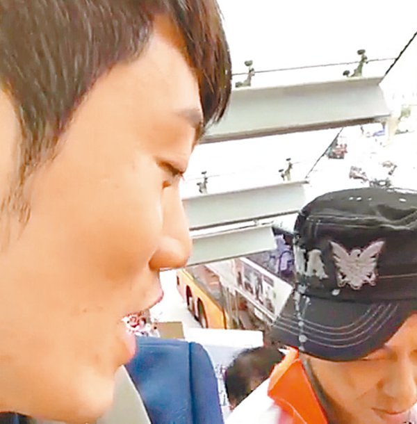 ■鄭松泰在金鐘港鐵站經行人天橋步行返立法會,四處向市民挑機,更洋洋自得地拍片直播。視頻截圖