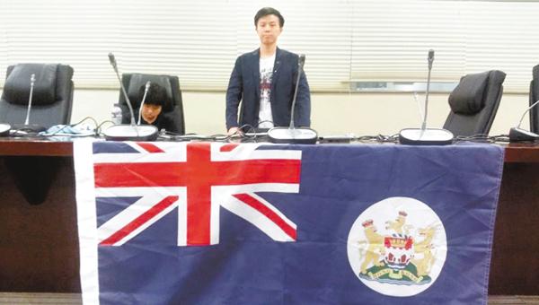 ■本月19日,「學動」召集人歐陽耀光在「中學生議會」上展示象徵「港獨」的「龍獅旗」。 網上圖片