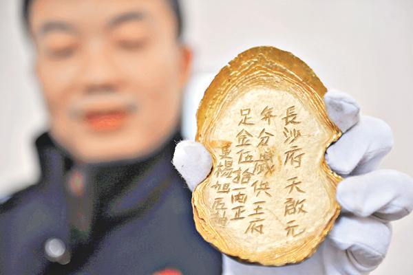 ■警方展示追回的五十�O金錠,上面刻有「長沙府天啟元年足金五十�O」等字樣。 資料圖片