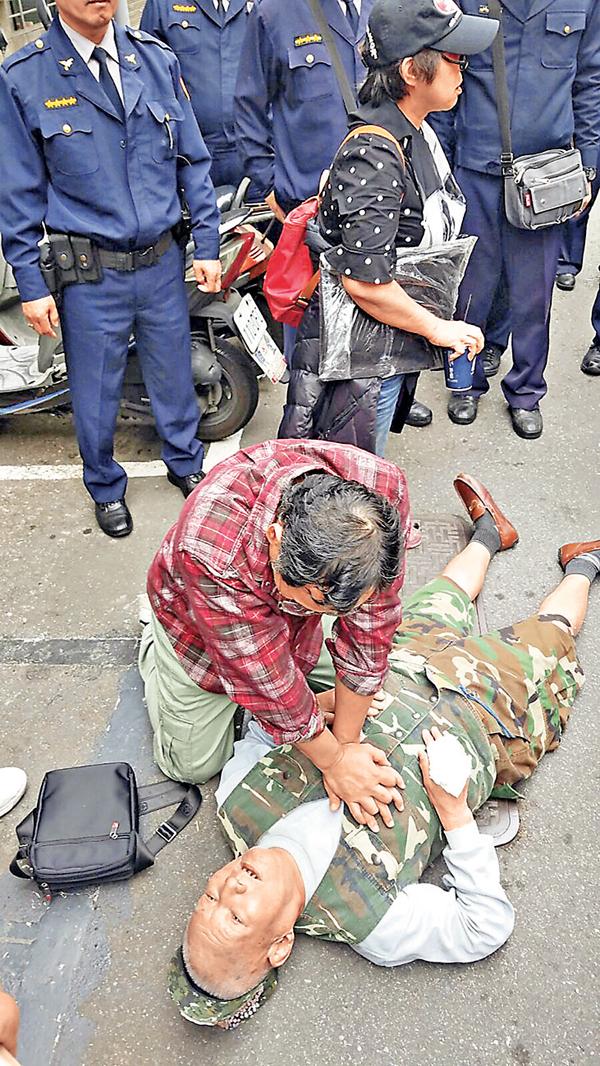 ■一名年長示威者被撞倒在地昏迷,由另一示威者在救護員到場前為他急救。 張得民  攝