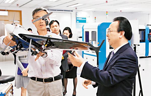 ■王煜(左)向譚鐵牛(右)展示研發中的「垂直起降固定翼飛機」。 潘達文  攝