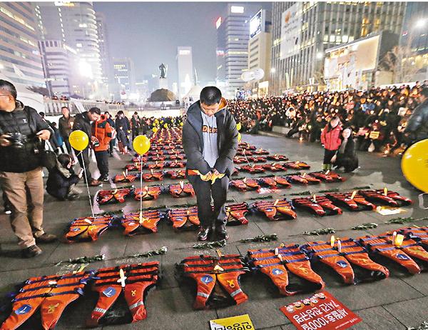 ■首爾有民眾向象徵遇難者的救生衣默哀。 美聯社