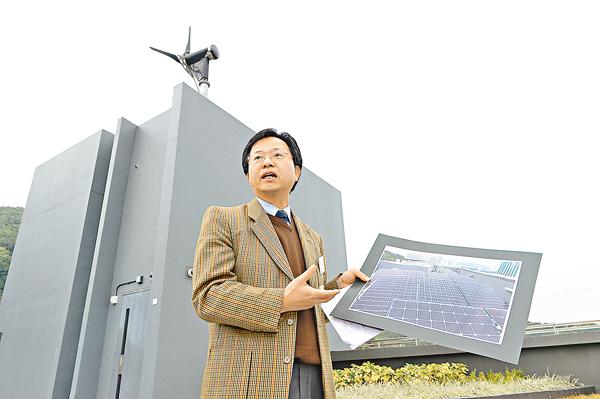 ■黃永根講解環保設施運作。左上為宿舍風力發電機組。校方供圖