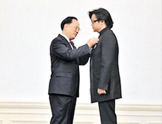何周禮(右)在2011年獲曾蔭權授勳(網絡圖片)