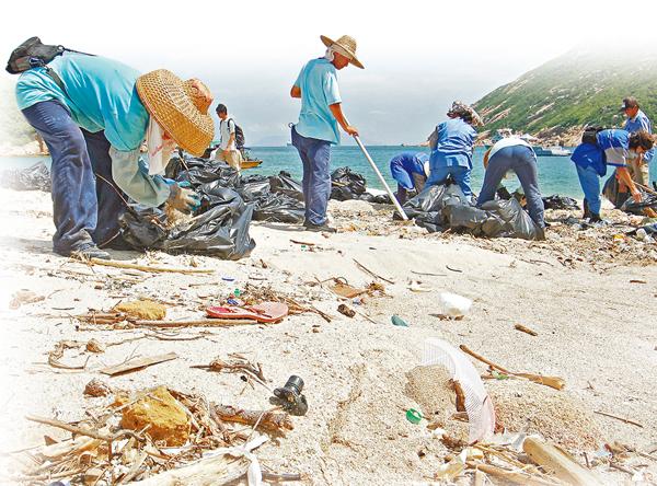 ■政府外判承包商職員在清理沙灘上的垃圾。 資料圖片
