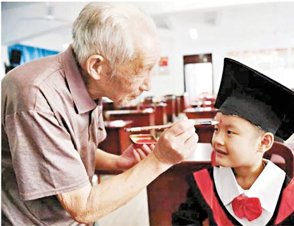 ■童中方在開學啟蒙禮上為學生點「聰明記」。    本報浙江傳真