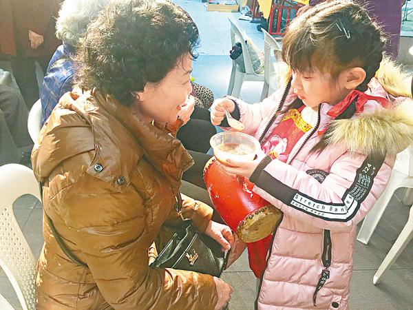 ■孩子為老人送粥的畫面,溫暖了福州的街頭。 記者何德花  攝