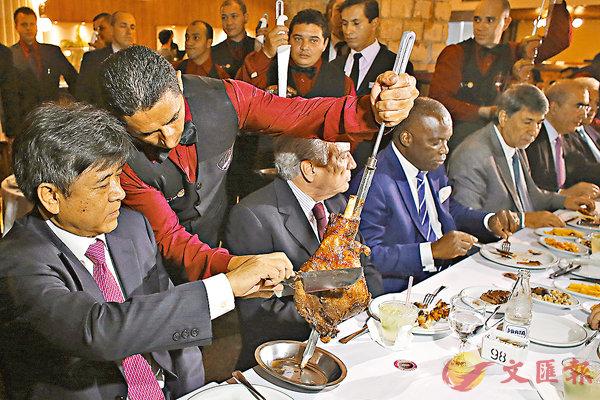 ■特默與各國大使食巴西牛扒,左一為中國大使。 美聯社