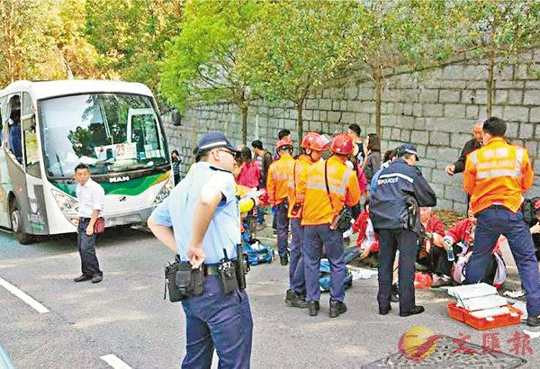■受傷乘客坐在路旁接受治理,左方為其中一輛涉事巴士。 網上圖片