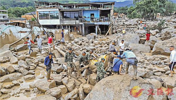 ■救援人員從泥石中搜救死傷者。法新社