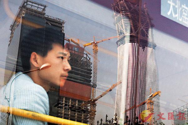 ■外媒認為內地經濟未來能否持續向好,取決於能否擺脫對房地產投資的依賴。圖為從北京公交車上的玻璃窗反射商務區的興建中樓宇。 美聯社