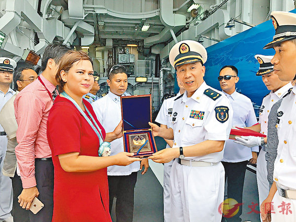 ■中國海軍艦艇編隊指揮員沈浩少將向登艦參觀的達沃市長薩拉.杜特爾特女士贈送紀念品。 中新社