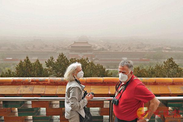 ■遊客在沙塵天氣中遊覽景山。 新華社
