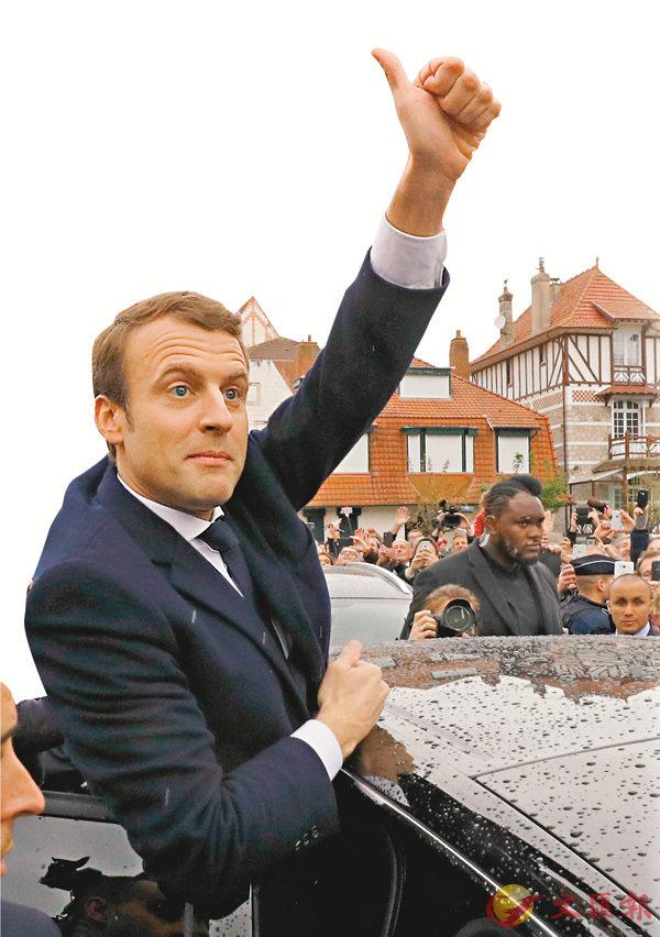 ■ 馬克龍投票後,在票站外高舉拇指,信心十足。 路透社