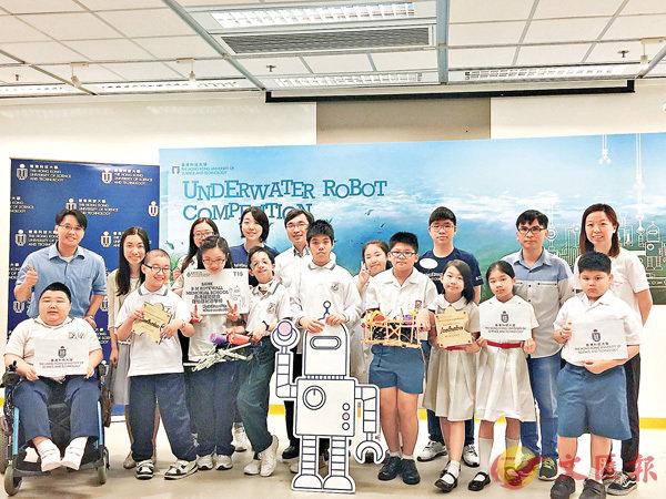 ■奪最佳團隊共融獎的保良局志豪小學和香港耀能協會羅怡基紀念學校的同學與自己製作的機器人、老師們合影。後排左五為胡錦添。 柴婧  攝