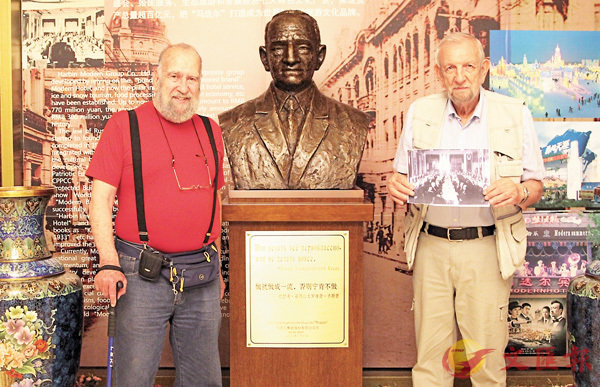 ■卡爾尼(右)手握爺爺的舊照片,與友人在馬迭爾賓館創始人雕像前合影。 香港文匯報哈爾濱傳真