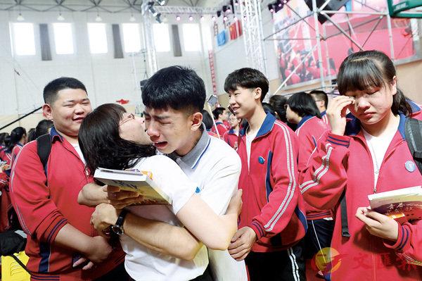 ■內蒙古某校舉辦畢業典禮,為高考生鼓勁。圖為學生與老師擁抱在一起。 中新社