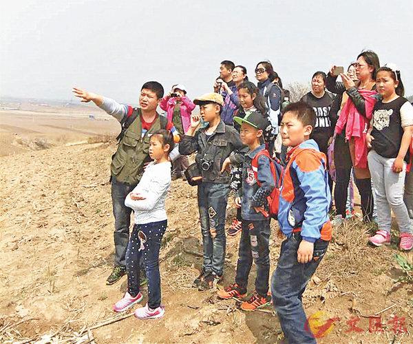 ■陳赫(前排揮手者)帶領青少年在田野考察,並講述城市歷史。 香港文匯報遼寧傳真