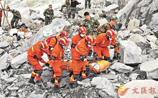■現場搜救仍在緊張進行。圖為救援人員運送遇難者遺體。 中新社