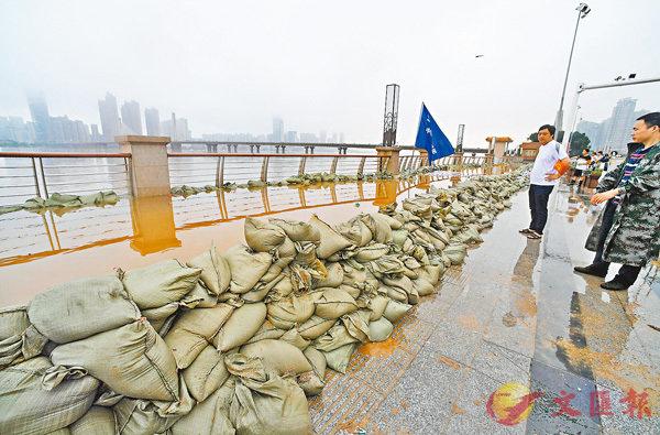 ■工作人員在長沙銀盆嶺大橋附近湘江沿岸堆積沙袋阻擋洪水。 新華社