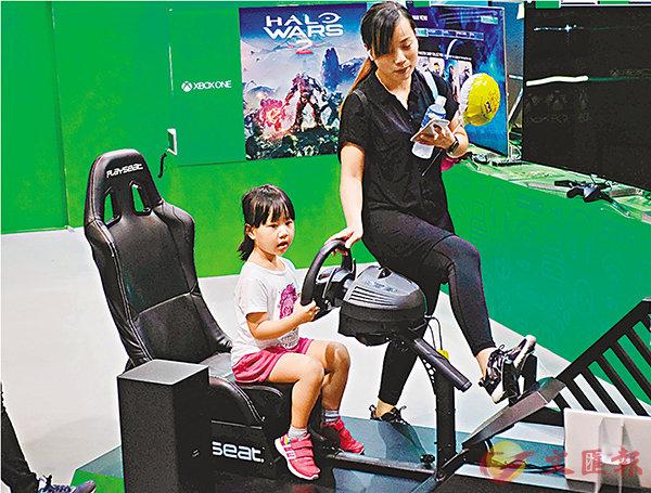 ■有小朋友於攤位試玩賽車遊戲,但因腿長不足踩油門,需攤位人員協助。 香港文匯報記者梁祖彝  攝