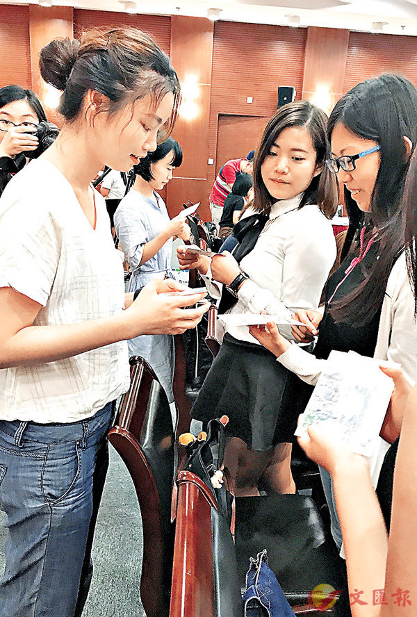 ■上海電氣志願者和實習生互換寫有祝福語的卡片。香港文匯報記者孔雯瓊  攝