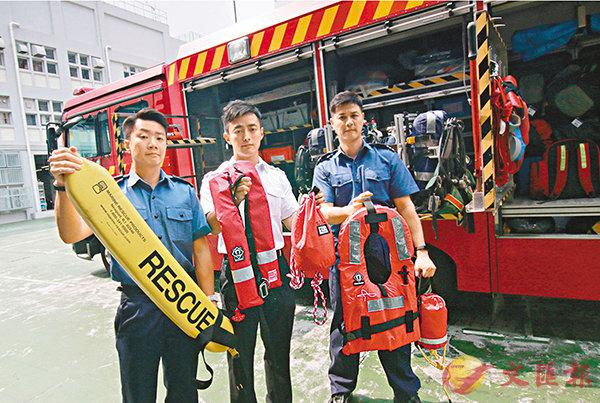 ■消防員(左起)孫逸興、潘崇晃、蔡河展示救生浮標及救生衣。 香港文匯報記者彭子文  攝