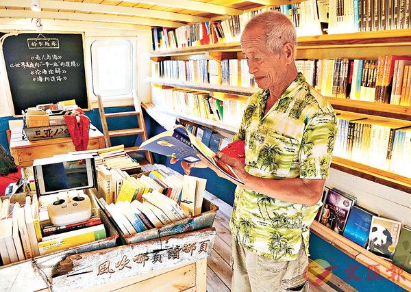 ■78歲的漁民陳木虎在「海上書房」翻看考古書籍。 中新社
