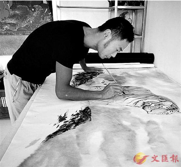 ■王燕飛在自家畫室裡一絲不苟地畫�茼悛瞗C  網上圖片