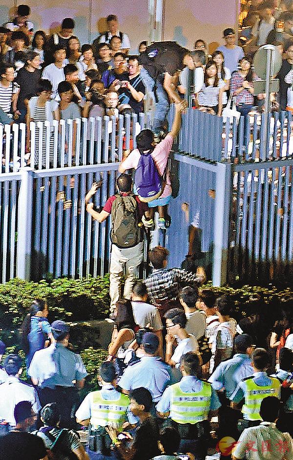 ■黃之鋒等「雙學三丑」曾煽動百餘人爬越圍欄硬闖政府總部(左圖),外圍亦有大批示威者與警方對峙。資料圖片